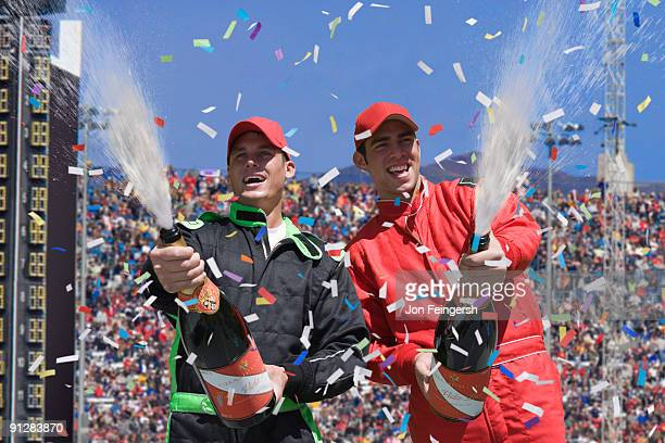 Winning race car drivers spraying champagne.