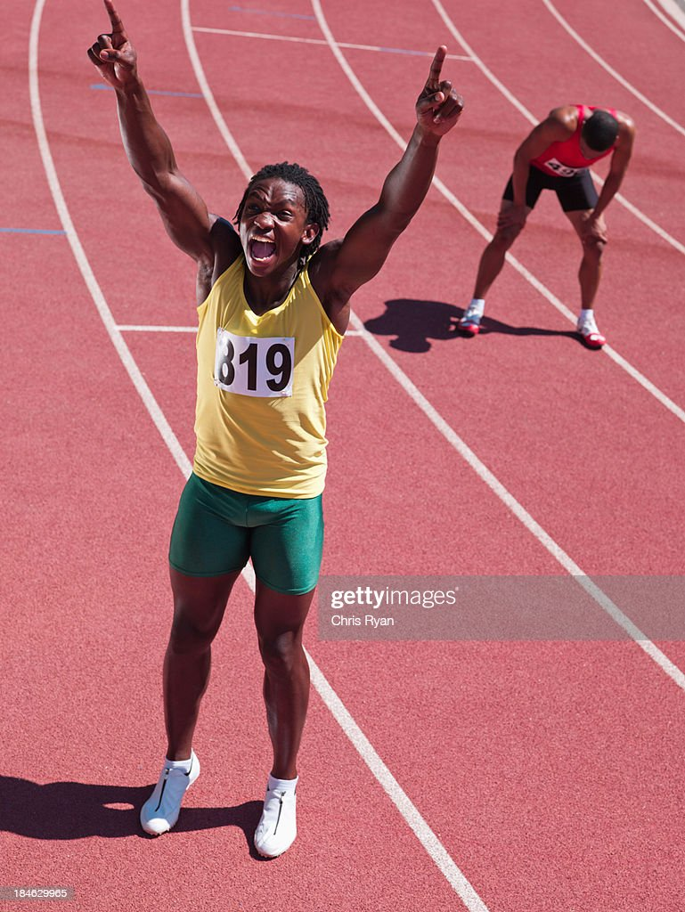 Winning racer cheering with tired competitor behind him : Stock Photo