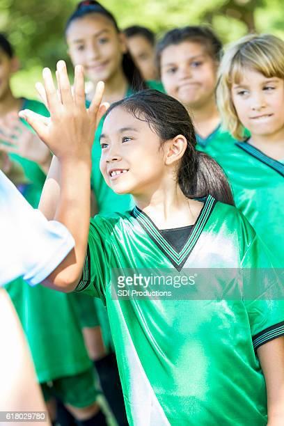 Winning soccer team gives opposing team high fives