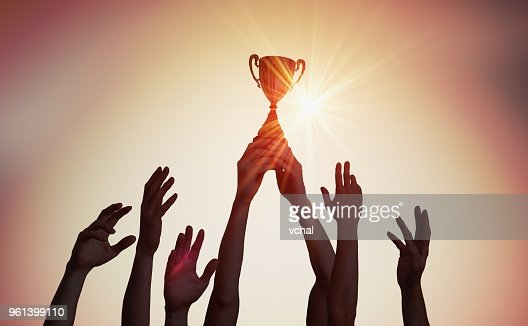 Winning team is holding trophy in hands. Silhouettes of many hands in sunset. : Stock Photo