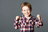 winning kid - winning young red hair child with a tooth missing raising his arms for happiness and excitement, grey background studio
