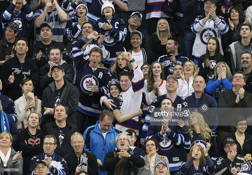 Winnipeg Jet fans cheer after the scoreboard ties, taking the game against the New York Islanders into overtime in NHL period action on January 27, 2013 at the MTS Centre in Winnipeg, Manitoba, Canada.