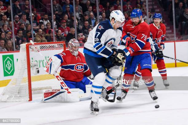 Winnipeg Jets center Adam Lowry and Montreal Canadiens defenseman Andrei Markov battle for the puck during the second period of the NHL regular...