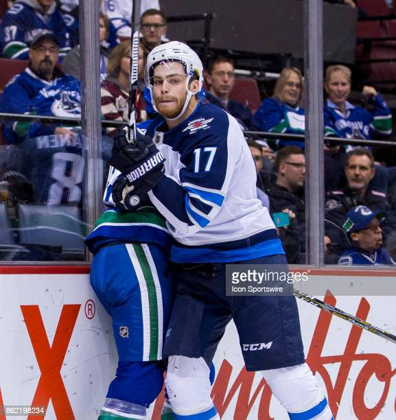Winnipeg Jets Center Adam Lowry checks Vancouver Canucks Right Wing Jake Virtanen in a NHL hockey game on October 12 at Rogers Arena in Vancouver BC