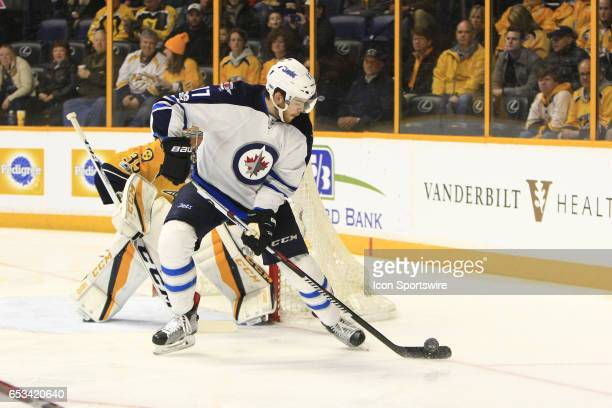 Winnipeg Jets center Adam Lowry gains control of the puck in front of Nashville Predators goalie Pekka Rinne during the NHL game between the...