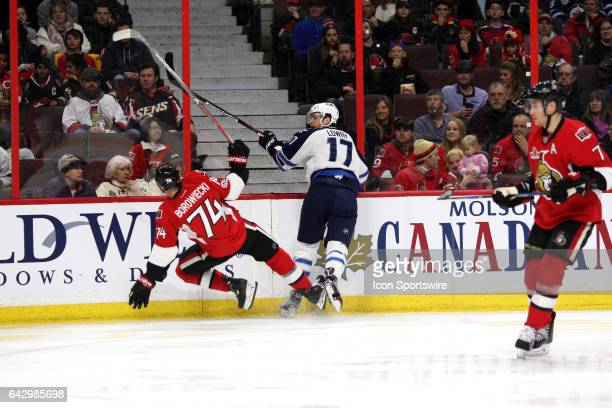 Winnipeg Jets Center Adam Lowry with a hit on Ottawa Senators Defenceman Mark Borowiecki during the first period in game between the Winnipeg Jets...
