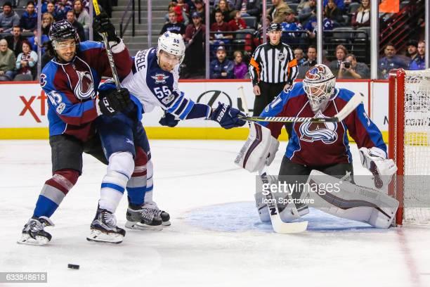 Winnipeg Jets Center Mark Scheifele fights for position against Colorado Avalanche Defenseman Mark Barberio as Colorado Avalanche Goalie Calvin...