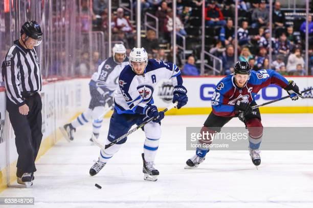 Winnipeg Jets Center Mark Scheifele skates with the puck as Colorado Avalanche Left Wing Gabriel Landeskog trails the play during the Winnipeg Jets...