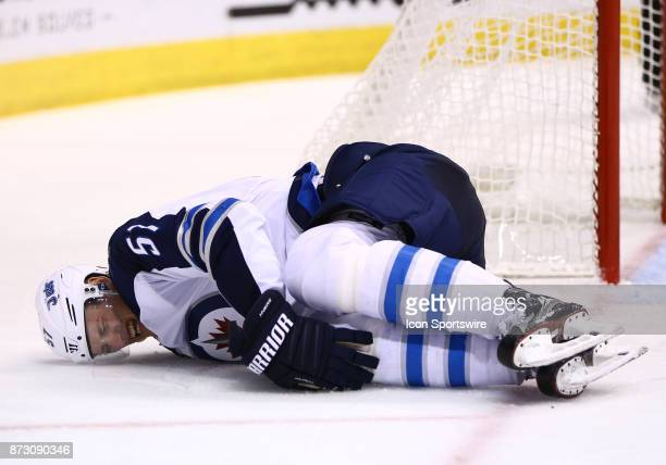 Winnipeg Jets defenseman Tyler Myers goes down with a knee injury during the NHL hockey game between the Winnipeg Jets and the Arizona Coyotes on...