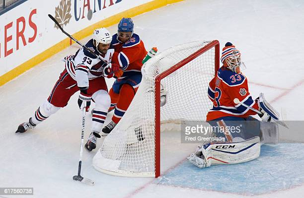 Winnipeg Jets Dustin Byfuglien attempts the wrap around on Edmonton Oiler goaltender Cam Talbot as he's checked by Darnell Nurse during the 2016 Tim...