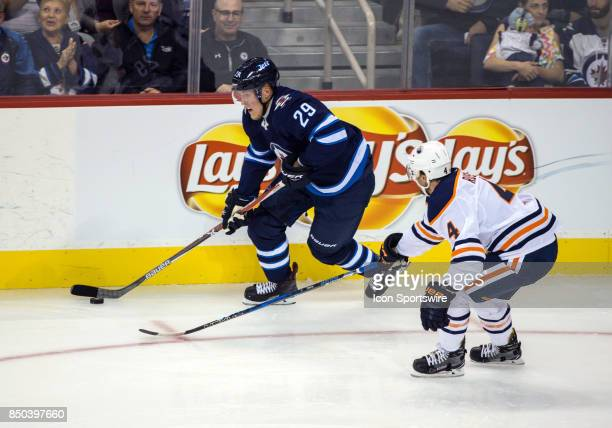 Winnipeg Jets forward Patrik Laine skates away from Edmonton Oilers defenseman Kris Russell during the NHL game between the Winnipeg Jets and the...