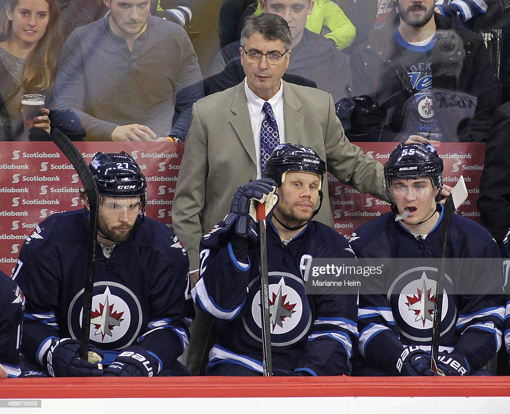 Winnipeg Jets' head coach Claude Noel watches from the bench behind players Eric Tangradi #27, Olli Jokinen #12 and Mark Scheifele #55 during third period action in an NHL game against the Columbus Blue Jackets at the MTS Centre on January 11, 2014 in Winnipeg, Manitoba, Canada.