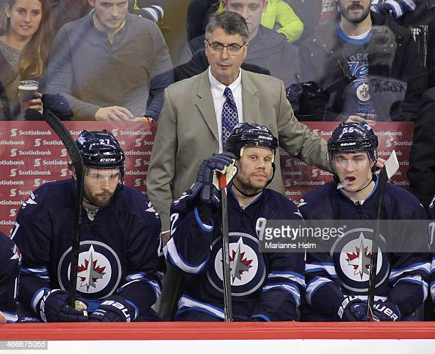 Winnipeg Jets' head coach Claude Noel watches from the bench behind players Eric Tangradi Olli Jokinen and Mark Scheifele during third period action...