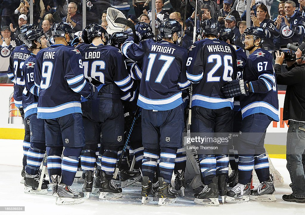 Winnipeg Jets players mob goaltender Ondrej Pavelec (not pictured) after a 4-3 shootout victory over the St. Louis Blues at the MTS Centre on October 18, 2013 in Winnipeg, Manitoba, Canada.