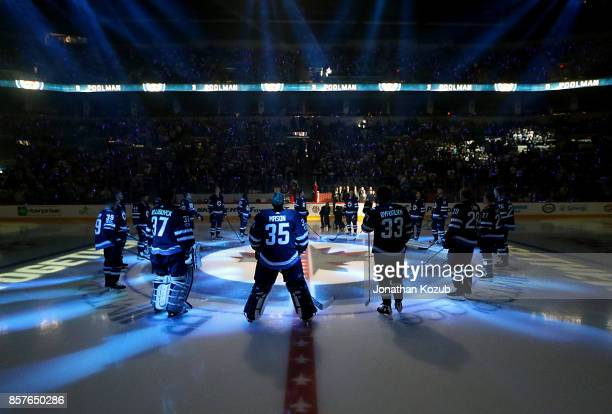 Winnipeg Jets players stand at centre ice during the player introductions prior to the home opener against the Toronto Maple Leafs at the Bell MTS...