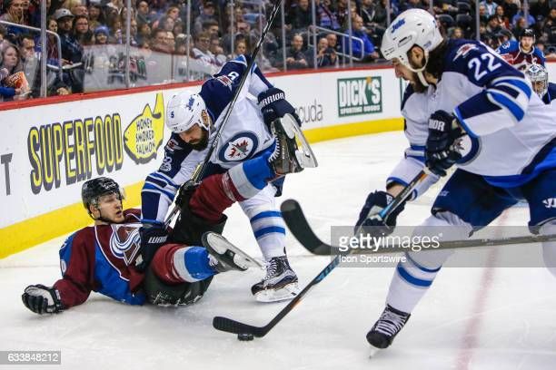Winnipeg Jets Right Wing Chris Thorburn clears the puck after Colorado Avalanche Center Nathan MacKinnon falls to the ice after being pushed by...