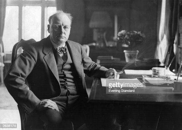 Winston Churchill seated at his desk at Chartwell