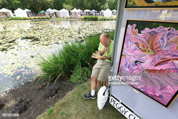 Winston Lumpkins of Brownville reads a book between his wife's kiosk at the Mill Creek pond during the Art in the Park Show Sale on Saturday in Mill...