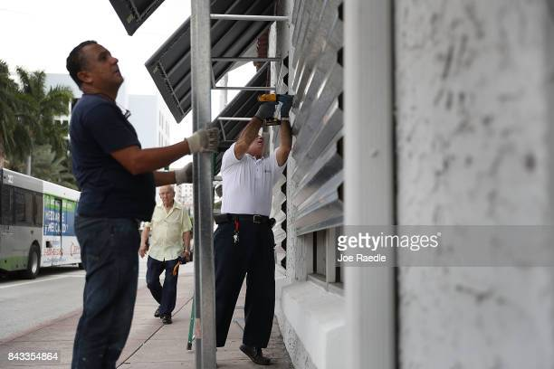 Winston Mora and Gus Sousa put hurricane shutters on a business as they prepare for Hurricane Irma on September 6 2017 in Miami Florida It's still...