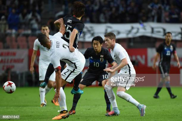 Winston Reid of New Zealand and Yuya Osako of Japan compete for the ball during the international friendly match between Japan and New Zealand at...