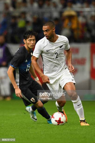 Winston Reid of New Zealand controls the ball under pressure of Kenyu Sugimoto of Japan during the international friendly match between Japan and New...