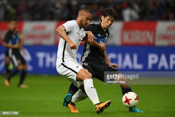 Winston Reid of New Zealand controls the ball under pressure of Yuya Osako of Japan during the international friendly match between Japan and New...