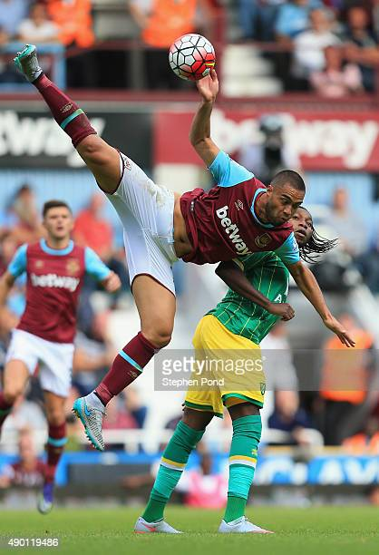 Winston Reid of West Ham United and Dieumerci Mbokani of Norwich City compete for the ball during the Barclays Premier League match between West Ham...