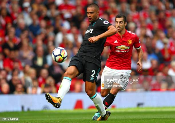 Winston Reid of West Ham United passes the ball under pressure from Henrikh Mkhitaryan of Manchester United during the Premier League match between...