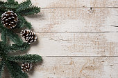 Top view of fir branch and snowy pine cones on white rustic table. High angle view of christmas fir tree on  wooden board with copy space. Winter frame with coniferous branches.