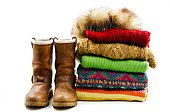 Winter boots, cap and stack of various sweaters. Winter style. Isolated on white background
