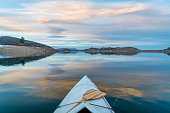 Horsetooth Reservoir near Fort Collins in northern Colorado, bow view from a decked expedition canoe with a wooden paddle, winter scenery at dusk