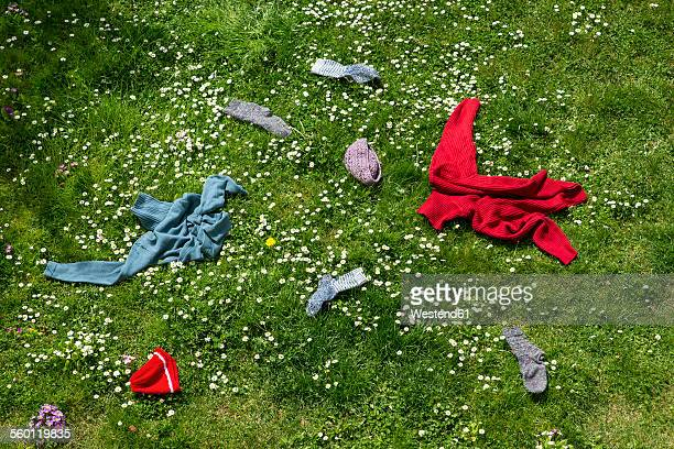 Winter clothes lying scattered in spring meadow