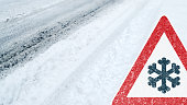 Winter Driving - snowy road with tire tracks and warning sign