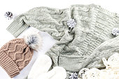 Winter fashion concept flat lay. Warm, cozy winter clothing, Christmas decorations on white background, top view