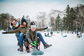 Gay (lesbian) parents and son enjoy in sledding on snow. Two young mothers and son