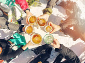 winter holidays - group of friends drinking beer on break at ski resort
