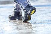 Winter legs wearing boots walking on snowy and sleet road