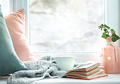 Winter life style background.Mug of tea, book,pillows on window sill empty copy space backdrop.Cold weather mood concept backdrop.