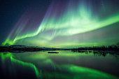 Northern lights blazing over lake Thingvellir national park in Iceland