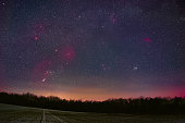 Winter night sky including Barnard's Loop, the Orion Nebula, the Flame Nebula, the Rosette Nebula, the California Nebula, and the Pleiades as seen from Battenberg in the Palatinate Forest in Germany.