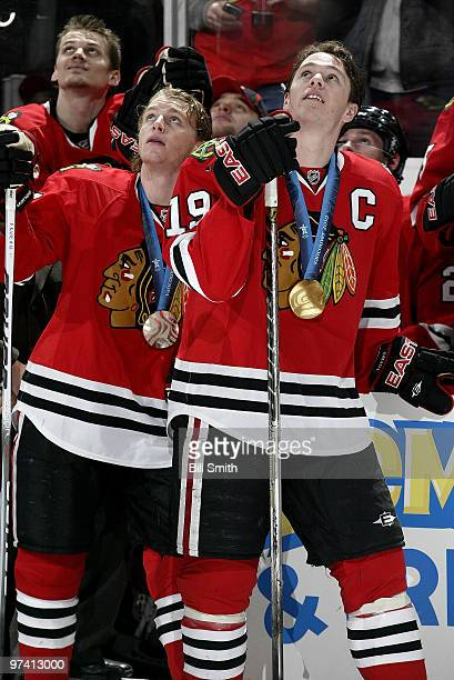 Winter Olympic silver medalist Patrick Kane and gold medalist Jonathan Toews of the Chicago Blackhawks watch the video board before a game against...