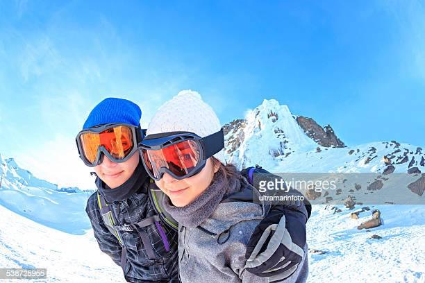 Winter play  Teenager boy and girl snow skiers enjoying