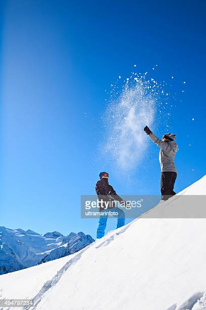 Winter playing   Boy and girl  skiers throwing snow  Snowball fight