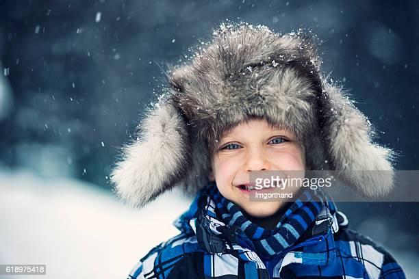 Winter portrait of cute little boy in big fur cap