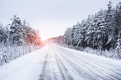 Winter road through the forest in countryside.