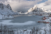 The classical view of fishing village Reine in winter with an extraordinary amount of snow and some ice on the fjord.