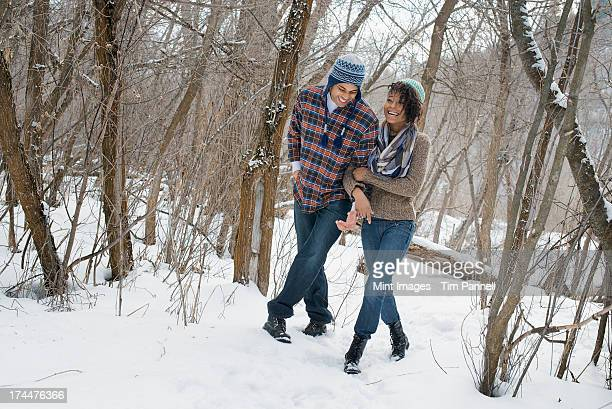 Winter scenery with snow on the ground. A couple arm in arm walking through the woods.
