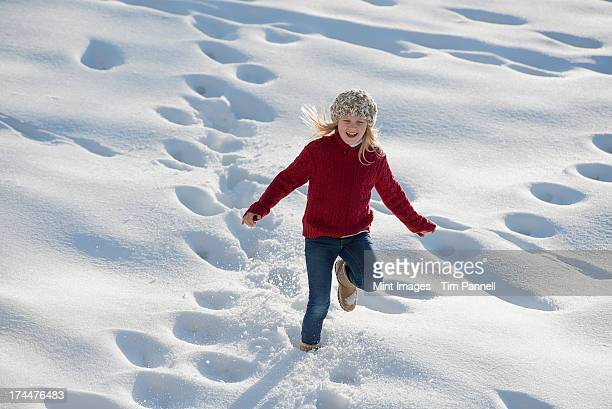 Winter scenery with snow on the ground. A young girl running through deep snow making footprint tracks.