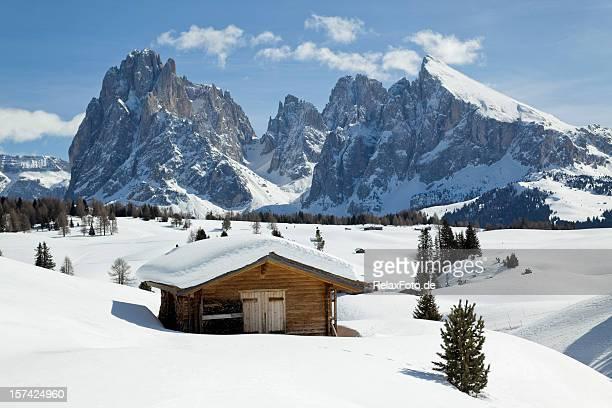 Paesaggio invernale in legno baracca e Langkofel-Sassolungo mountain (Dolomiti, Italia