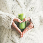 Winter seasonal smoothie drink detox. Female in sweater holding bottle of green smoothie or juice making heart shape with her hands, square crop. Clean eating, weight loss, healthy dieting food concep